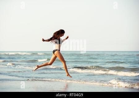 Happy beautiful slim lady runs at sea beach - Stock Image