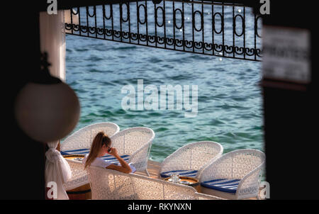 Girl reading a book in seaside cafe by the deep blue Mediterranean Sea in Montenegro. - Stock Image