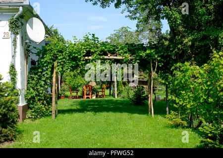 well kept house garden with an abundance of greenery in the rural village of szatta vas county hungary - Stock Image