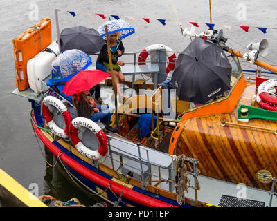 Passengers on the old Whitby Lifeboat 'Mary Ann Hepworth' in Whitby harbour waiting to go on a summer pleasure trip  umbrellas up in heavy rain - Stock Image