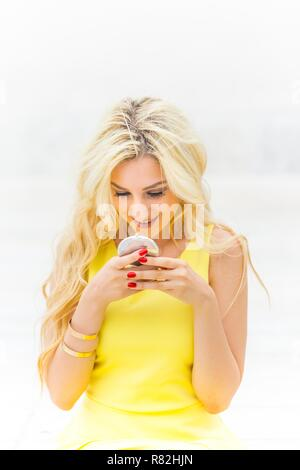 Facing camera high-key photo of young 20s blonde woman beauty looking down at handy mirror smiling at herself being pretty - Stock Image