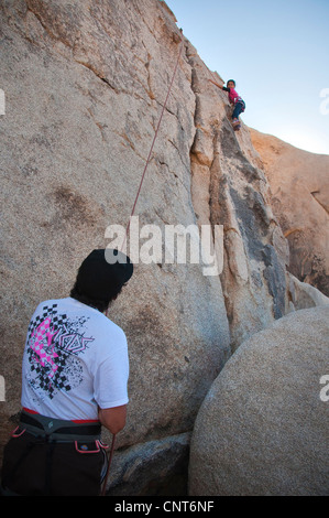 father daughter young girl rock climbing climb risk rope wall child sport - Stock Image