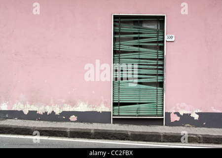 A small door with an old green blind in the doorway. Doorway set against a light pink wall in Sicily, Italy - Stock Image