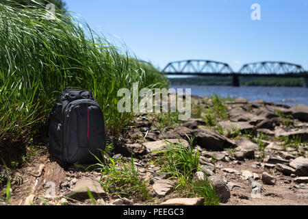 Camera Bag by River Bridge in Background - Stock Image