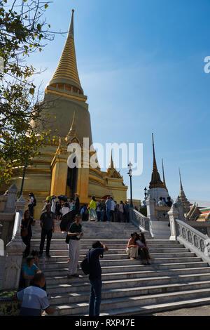 Tourists near Phra Si Rattana Chedi in the Emerald Budda Temple, Bangkok, Thailand - Stock Image