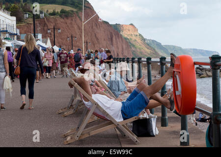 The promenade at Sidmouth sea front during the folk festival 2014. Man in deckchair on mobile phone. - Stock Image