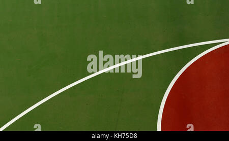 Pole aerial image of an outdoor basketball court. Abstract shapes created by red key, white lines and green surface. - Stock Image