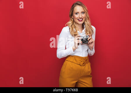 Beautiful happy young blonde woman standing isolated over red background, holding photo camera - Stock Image