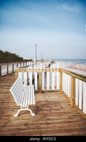 Empty bench on a wooden boardwalk by a beach. - Stock Image