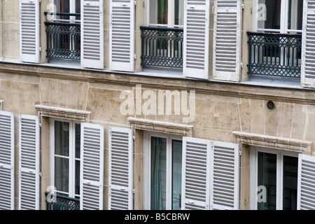 Façade windows shutters Juliet balcony metal stone building apartment condo repetition louvered paris france - Stock Image