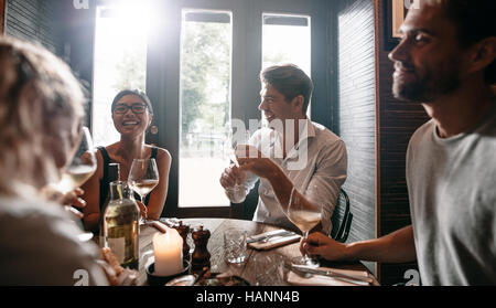 Young men and women having wine at restaurant. Group of friends drinking wine at a bar. - Stock Image