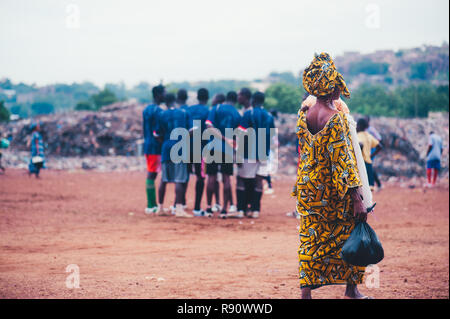 Mali, Africa - Black african children playing soccer in a rubbish dump with their parents crossing the game field. Rural area near Bamako - Stock Image