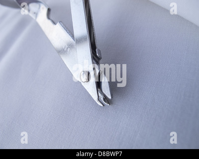 Surgical instrument for removing surgical clips from healed surgical incisions. Showing details if tines which grip - Stock Image