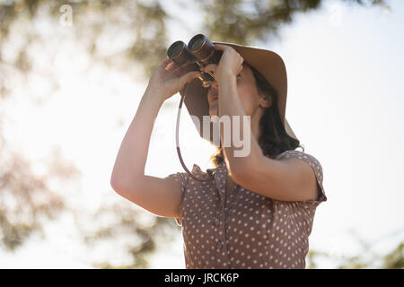 Senior woman looking through binoculars - Stock Image