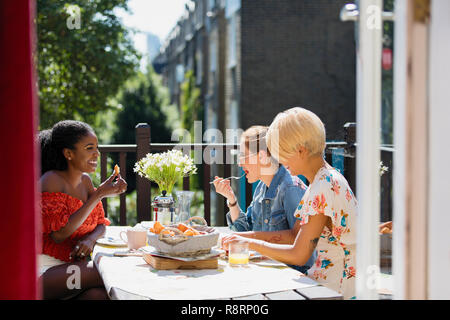 Young women friends eating brunch on sunny apartment balcony - Stock Image