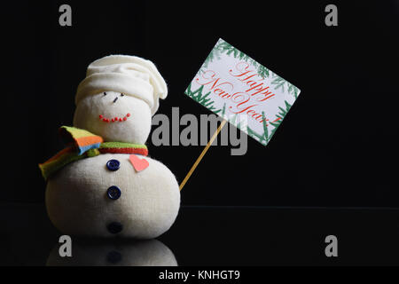 """Snowman figure holding placard board with stick attached and text """"Happy New Year!"""" written on it, surrounded with - Stock Image"""