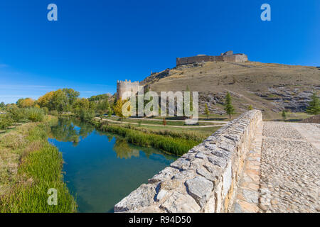scenary with roman bridge and ruins of castle, landmark and public monument from tenth century, in Burgo de Osma, Soria, Spain, Europe, reflected on w - Stock Image