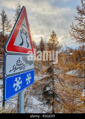 Alpine road in winter with snow warning sign - Stock Image