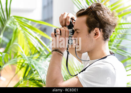 Man taking photo, palm plant in background - Stock Image