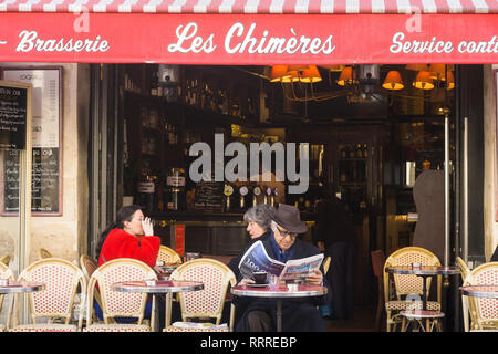 Patrons reading newspapers and having coffee at Brasserie Les Chimeres in the Marais district of Paris, France. - Stock Image