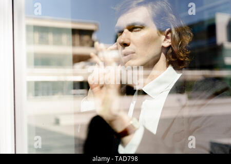 Italy, Florence, young businessman behind a window on smartphone - Stock Image