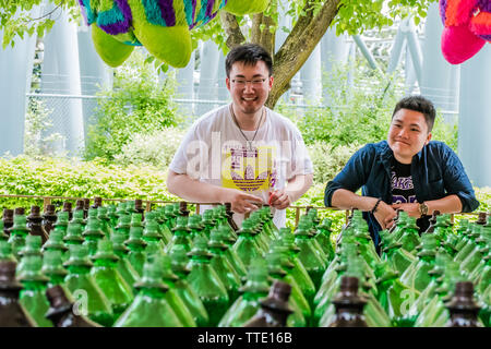 happy asian man playing ring toss game inside an amusement park - Stock Image