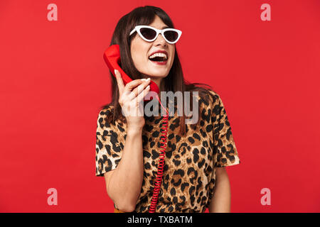 Image of a beautiful laughing young woman dressed in animal printed shirt posing isolated over red background wearing sunglasses talking by telephone. - Stock Image