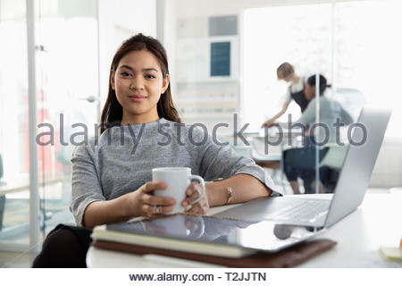 Portrait confident businesswoman drinking coffee at laptop in office - Stock Image