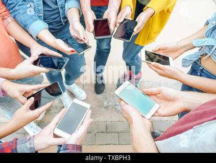 Group of friends using their smart mobile phones - Millennial young people addicted to new technology trends - Stock Image