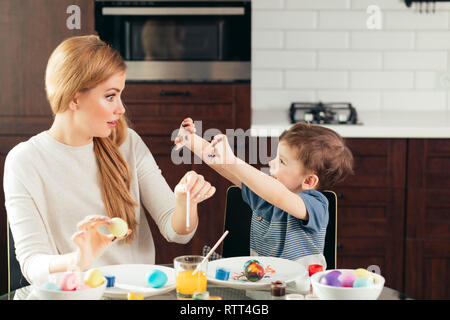 Cute little male kid shows his shocked surprised young mother his small palms, all smeared in paint after decorating Easter eggs. Mother and son prepa - Stock Image