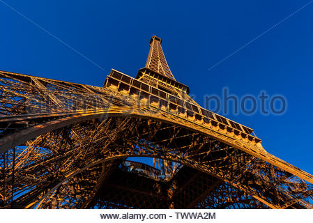 Looking up at the Eiffel Tower from directly underneath it. The world famous wrought-iron lattice tower is the most famous landmark of Paris, France. - Stock Image