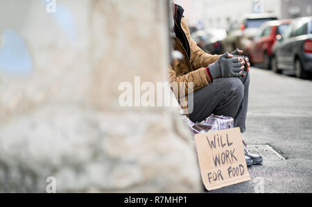 A midsection view of homeless beggar man with a carboard sign sitting outdoors in city asking for money donation. Copy space. - Stock Image