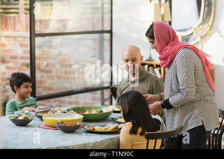 Mother in hijab serving dinner to family at dining table - Stock Image
