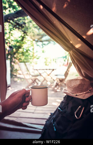 vertical view of a hand of a hiker man resting with a cup in a camping tent, travel discovery concept, point of view shot - Stock Image