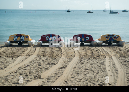 Four (4) red and yellow pedalos on the sandy beach at Swanage, Dorset, positioned near the sea - Stock Image