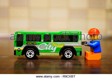 Poznan, Poland - December 22, 2018: Lego construction worker trying to repair a Mattel Matchbox city bus in soft focus background.  - Stock Image