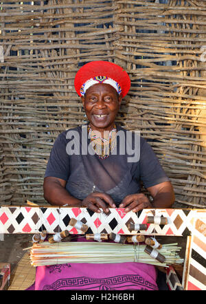 Shakaland Zulu woman in traditional Zulu hat shows her skill at weaving for the tourists at the Shakaland Cultural - Stock Image