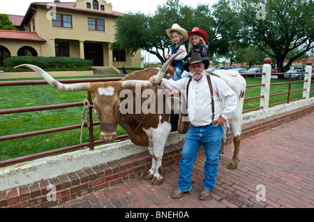 Children  on longhorns posing with grandfather in Fort Worth, Texas, USA - Stock Image