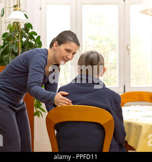 Rear view of a senior woman sitting at home talking to a younger woman from a domestic care service who is helping her during the day, text space - Stock Image