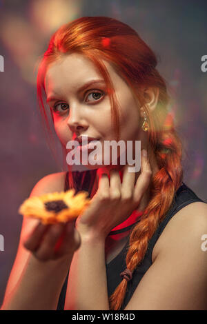 Red-haired smiling girl with a long braid holds a flower in her hand - Stock Image