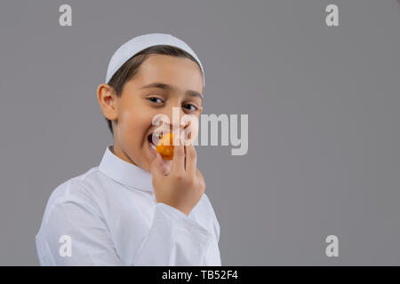 Young Muslim boy wearing cap smiling and eating sweets - Stock Image