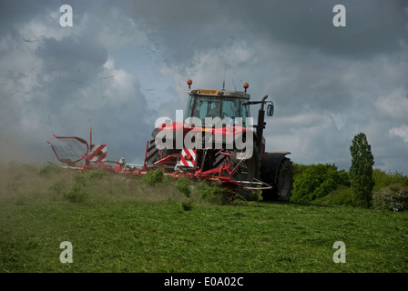 Tractor turning grass to dry for silage in British countryside in spring - Stock Image