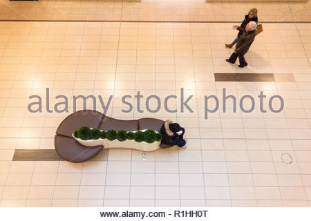 Connected but alone due to smart phone device technology and relationships at the shopping mall in Canada - Stock Image