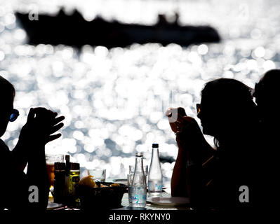 Tourists eating seafood in a seaside restaurant by the Mediterranean Sea. - Stock Image
