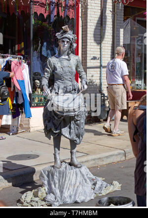 ASHEVILLE, NORTH CAROLINA, USA – 9/5/2010: A popular human statue known as the Silver Drummer Girl busks in downtown Asheville, holding still then com - Stock Image