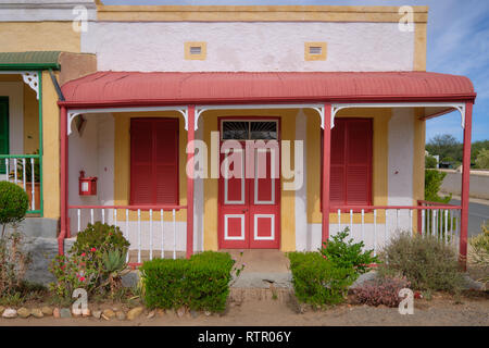 Traditional Karoo home architecture. Red and yellow flat roof house, with crooked awning. In Prince Albert, South Africa - Stock Image