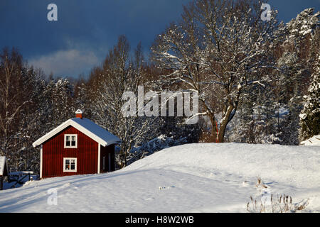 old red cottage in a snowy winter landscape, - Stock Image