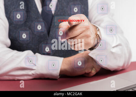 man sitting at desk touching cyber security on a virtual screen. - Stock Image