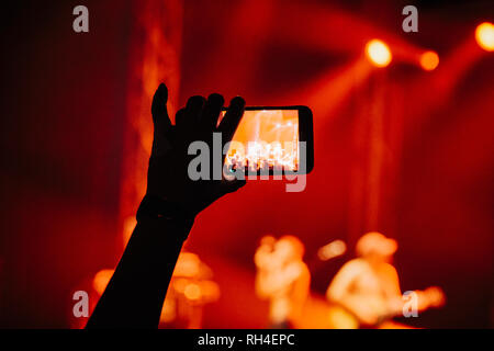 Hand in audience video recording musical concert with camera phone - Stock Image