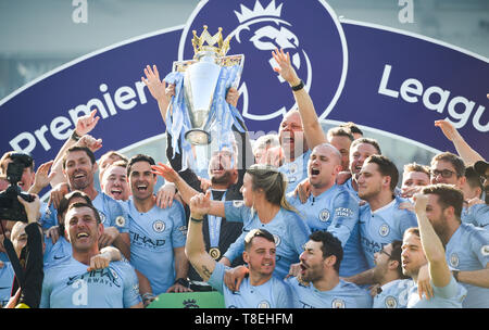 Manchester City manager Pep Guardiola lifts the Premier League trophy with his staff after the Premier League match between Brighton & Hove Albion and Manchester City  at the American Express Community Stadium 12 May 2019 Photograph taken by Simon Dack  Editorial use only. No merchandising. For Football images FA and Premier League restrictions apply inc. no internet/mobile usage without FAPL license - for details contact Football Dataco - Stock Image